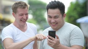 Two young multi-ethnic handsome men together in the streets outdoors. Portrait of two young multi-ethnic handsome men together in the streets outdoors stock video