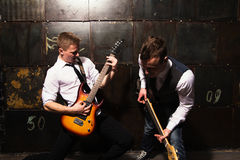 Portrait of Two young musicians  with guitar on black background Stock Image
