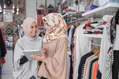 Two muslim business partner. Portrait of a two young muslim business team with beautiful smile holding digital tablet while standing in their fashion boutique royalty free stock photography