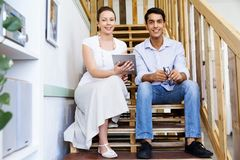 Portrait of two young people sitting at the stairs in office Stock Photos