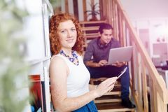 Portrait of two young people sitting at the stairs in office Royalty Free Stock Image