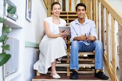 Portrait of two young people sitting at the stairs in office Stock Images