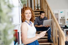 Portrait of two young people sitting at the stairs in office Royalty Free Stock Images