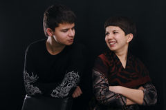 Portrait of two young peoples. Talking and smiling over black. Brother and sister Stock Photo