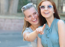 Portrait of two young positive woman looking ahead and show something each other. Portrait of two young positive women looking ahead and show something each Royalty Free Stock Image