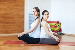 Portrait of two young pregnant women in sport clothes sitting cross-legged, in a sports fitness center. Yoga meditation Royalty Free Stock Photos
