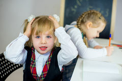 Portrait of two young schoolgirls sitting at the table Stock Photography