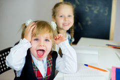 Portrait of two young schoolgirls sitting at the table Royalty Free Stock Photos