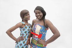 Portrait of  two young smiling women with hands on their hips in traditional dresses from Africa, studio shot Stock Images