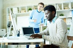 Two IT Specialists Working in Office. Portrait of two young specialists, one of them African-American, working together in modern office discussing projects Royalty Free Stock Photo