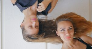 Two young woman with flying hair. Portrait of two young strange woman with flying hair stock footage