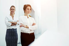 Portrait of two young successful female leaderships in formal wear standing with crossed arms in office interior, Royalty Free Stock Photo