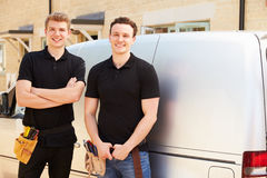 Portrait of two young tradesmen by their van Stock Images
