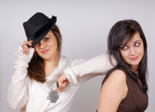 Portrait of two young women. A beautiful girl wearing a white pullover and a black hat is putting her arm on the shoulder of her friend. Horizontal color image Stock Photos