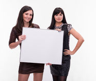 Portrait of two young women with billboard Royalty Free Stock Photo
