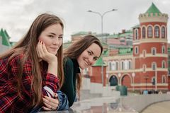 Portrait of two young women in casual wear on a walk around the city, standing and looking at the camera.  Stock Photos
