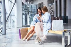 Young Women in Shopping Center Hall. Portrait of two young women chatting happily sitting on bench in shopping mall with paper bags and using smartphone Stock Images