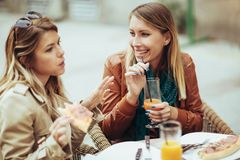 Portrait of two young women eating pizza outdoors Stock Photo