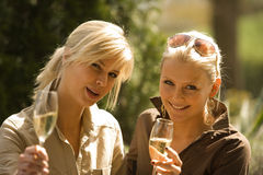 Portrait of two young women holding champagne flutes and smiling Royalty Free Stock Photo
