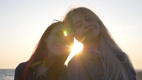 Portrait of two young women leaning head to head against the sea with sunbeams and highlights