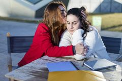 Portrait of two young women in an outdoor cafe while hugging stock image