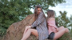 Portrait of two young women. On a rock during sunset stock video footage