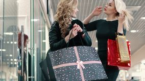 Portrait of two young women shopping at the mall. Two young women show each other their purchases at the mall stock video footage