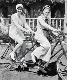 Portrait of two young women sitting on a tandem bicycle Royalty Free Stock Photos