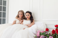 Portrait of two young women in wedding dresses in White Hall royalty free stock images