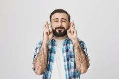 Portrait of typical adult european man with beard and moustache in checked shirt, crossing fingers and expressing. Willingness for something to happen with Royalty Free Stock Images