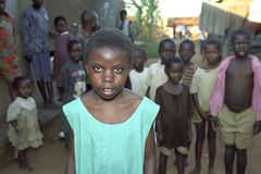 Portrait of Ugandan girl with friends in background. Uganda, village Kalasa: a child poses proudly and shy because she is the centerpiece while her boyfriends stock photos