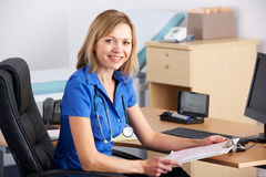 Portrait UK doctor sitting at desk Stock Photo