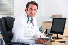 Portrait UK doctor sitting at desk Royalty Free Stock Image