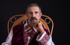 Portrait of Ukrainian country-man sitting in a wicker chair, wearing traditional clothes Vyshyvanka Stock Photos