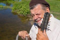 Portrait of Ukrainian senior squinted sitting on a riverside Stock Images