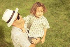 Portrait un père et un fils s'asseyant sur l'herbe Photographie stock libre de droits