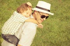 Portrait un père et un fils s'asseyant sur l'herbe Photographie stock