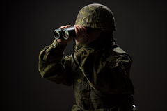 Portrait of unarmed woman with camouflage. Young female soldier observe with binoculars. Stock Photo
