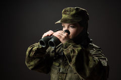 Portrait of unarmed woman with camouflage. Young female soldier observe with binoculars. Stock Images