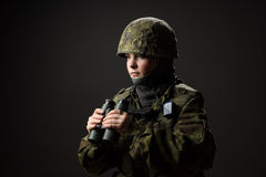 Portrait of unarmed woman with camouflage. Young female soldier observe with binoculars. stock photos