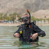 Portrait of underwater diver in basic equipment dives before deep diving. Lessons of underwater diving. Popular water sport and stock photography