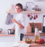 Portrait une femme de sourire avec le téléphone dans la cuisine à la maison Photo libre de droits