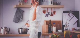 Portrait une femme de sourire avec le téléphone dans la cuisine à la maison Images libres de droits
