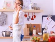 Portrait une femme de sourire avec le téléphone des légumes dans la cuisine à la maison Photos stock
