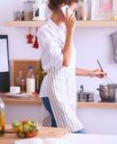 Portrait une femme de sourire avec le téléphone des légumes dans la cuisine à la maison Photo stock