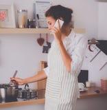Portrait une femme de sourire avec le téléphone des légumes dans la cuisine à la maison Images libres de droits