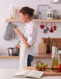 Portrait une messagerie textuelle de sourire de femme des légumes dans la cuisine à la maison Photographie stock libre de droits