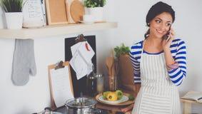Portrait une messagerie textuelle de sourire de femme des légumes dans la cuisine à la maison Image libre de droits
