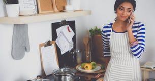 Portrait une messagerie textuelle de sourire de femme des légumes dans la cuisine à la maison photos stock