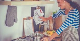 Portrait une messagerie textuelle de sourire de femme des légumes dans la cuisine à la maison photographie stock